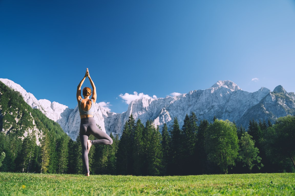 Woman practicing yoga in the mountains